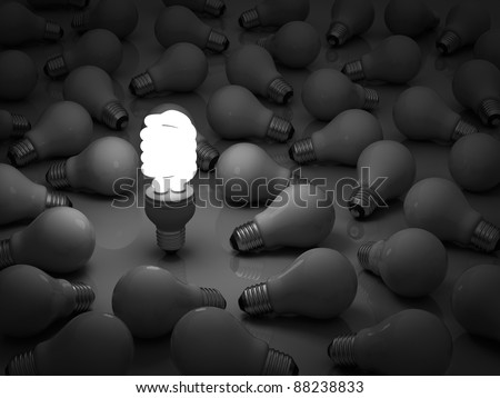 It's time for energy saving light bulb, one glowing compact fluorescent light bulb standing out from the unlit incandescent bulbs - stock photo