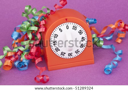 It's time to party! Clock and streamers on purple. - stock photo