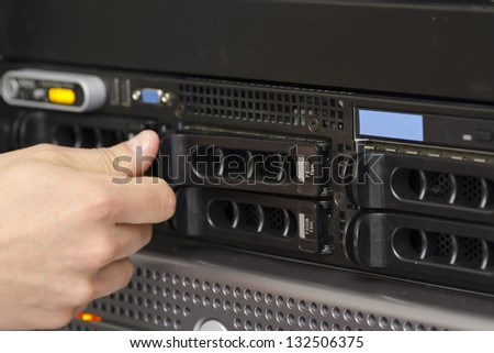 """IT technician / consultant insert / remove a hard disk from a blade server data center. This is a 3,5"""" hard drive. - stock photo"""