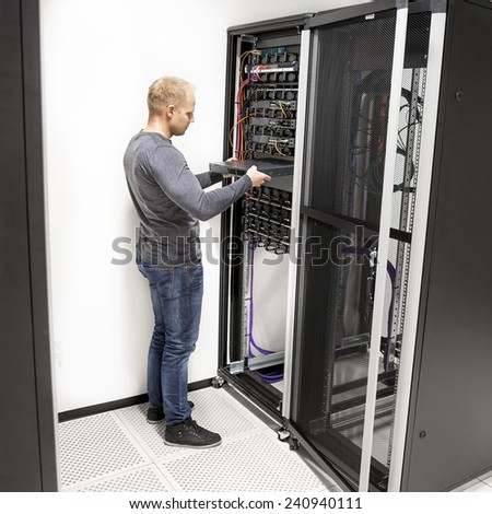 IT technician install network rack in datacenter