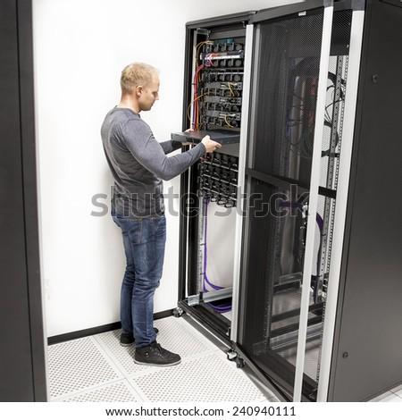 IT technician install network rack in datacenter - stock photo