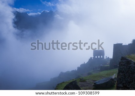 It was early in the morning and foggy. All of a sudden, a hole opened up in the sky showing the peaks of the majestic mountains surrounding the site. The heaven seems so close yet impossible to reach. - stock photo
