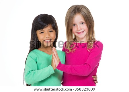 italian and asian little girl smiling looking at the camera - stock photo