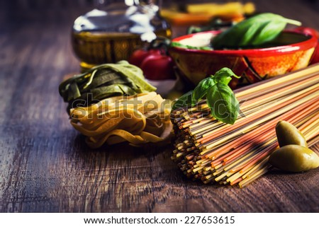 Italian and Mediterranean food ingredients on old wooden background.spaghetti olives basil pesto pasta garlic pepper olive oil and mortar. - stock photo