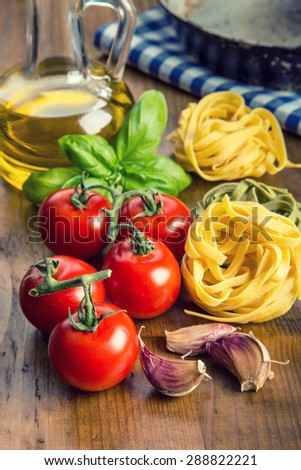 Italian and Mediterranean food ingredients on wooden background.Cherry tomatoes pasta, basil leaves and carafe with olive oil. Wooden and old  kitchen utensils - stock photo