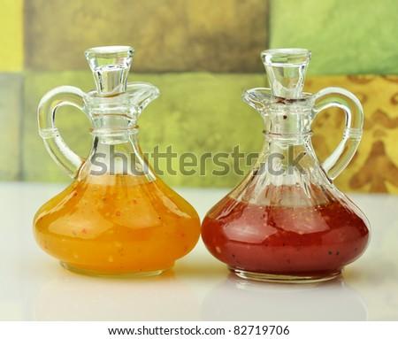 italian  and raspberry vinaigrette salad dressings in glass bottles - stock photo