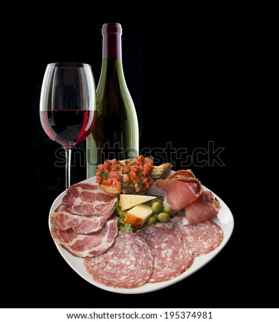 Italian antipasto with ham, olive, tomato, cheese, bread,  salami and a lovely Chianti red wine - stock photo