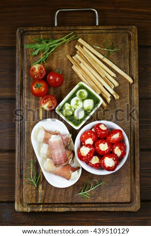Italian appetizer antipasti made dish - ham, cheese, peppers - stock photo