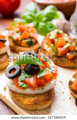 Italian Appetizer Bruschetta with roasted tomatoes, mozzarella cheese, black olives and herbs - stock photo