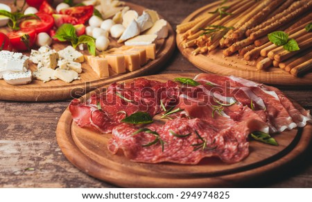 Italian appetizer - various types of ham, cheese and grissini - stock photo