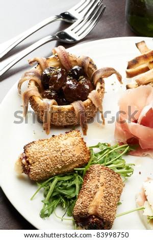 italian appetizer with ham , mozzarella and arugula - stock photo