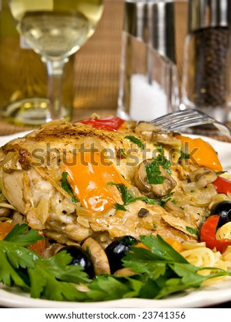 Italian Baked Chicken on a plate served with pasta. - stock photo