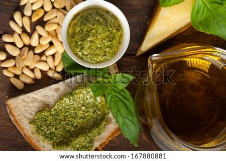 Italian basil pesto bruschetta ingredients over old wood macro - stock photo