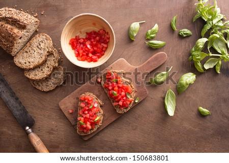 Italian bruschetta on wooden table overview - stock photo