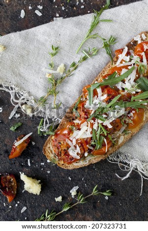 italian bruschetta with baked cherry tomatoes, parmesan cheese and rocket on toasted slice of bread - stock photo