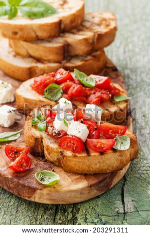 Italian bruschetta with chopped tomatoes, basil and cheese on grilled crusty bread - stock photo