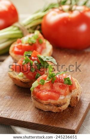 Italian bruschetta with tomatoes onion and basil, rustic food - stock photo