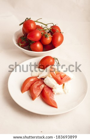 Italian Buffalo mozzarella cheese and red tomatoes on a white background