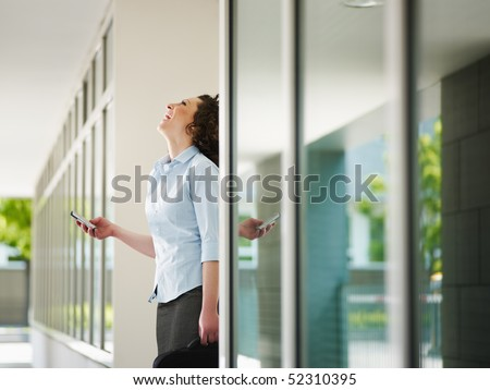 italian business woman standing out of office building and reading emails on mobile phone. Horizontal shape, Copy space - stock photo