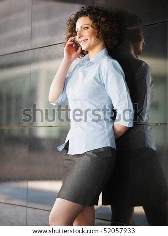 italian businesswoman talking on mobile phone outdoors and smiling. Vertical shape - stock photo
