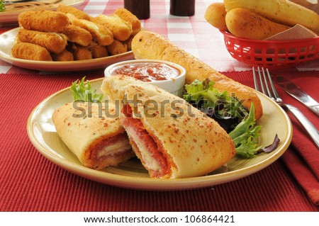 Italian calzones with bread and cheese sticks - stock photo