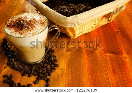Italian cappuccino in a glass cup with coffee beans on background - stock photo