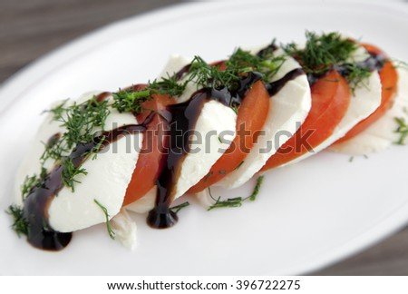 Italian Caprese Salad with a twist, adding dill and creamy Balsamic vinegar. - stock photo