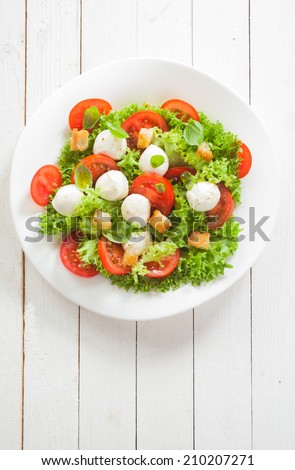 Italian Caprese salad with mozzarella pearls and tomato on a bed of lettuce garnished with golden crunchy friend bread croutons, overhead view on white boards with copyspace - stock photo