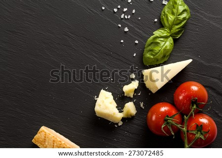 Italian Cheese on black stone background with basil and tomatoes - stock photo