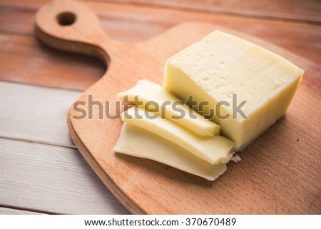 Italian cheese sliced on a wooden board