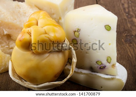 Italian cheeses on a wooden table, rustic