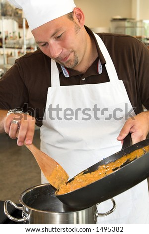 Italian chef moving pasta into another pan - stock photo