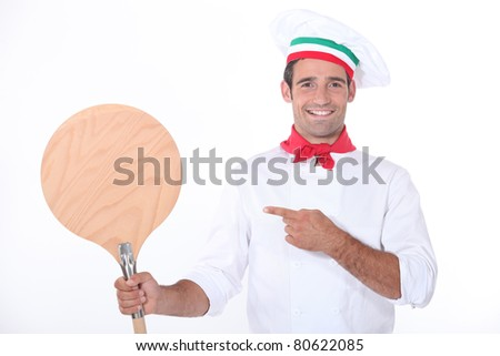 Italian chef pointing at a wooden pizza peel - stock photo