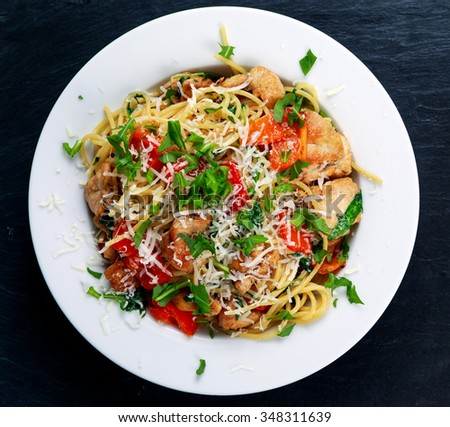 Italian Chicken Breast spaghetti with red pepper, Parmesan cheese and wild rocket  lives. on old blue stone background. - stock photo