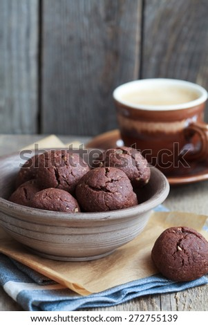Italian chocolate cookies with walnuts and a cup of coffee on a wooden table, rustic style, selective focus