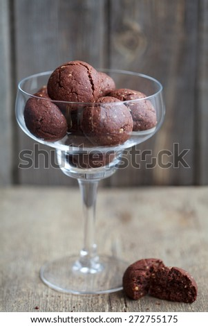 Italian chocolate cookies with walnuts in a wine glass on a wooden table, rustic style, selective focus - stock photo