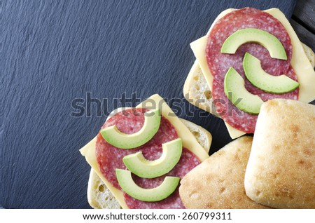Italian ciabatta sandwich with salami, cheese and avocado on on black stone as background or texture - stock photo