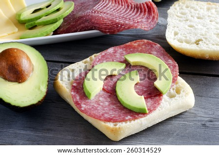 Italian ciabatta sandwich with salami, cheese and avocado on wooden background - stock photo