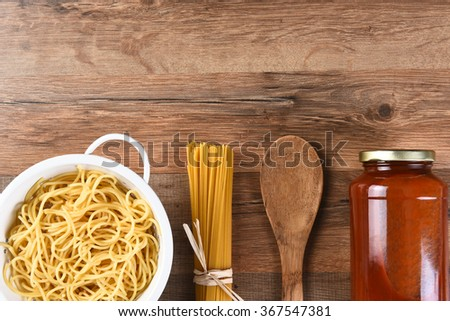 Italian Cooking Still Life with copy space. Wooden spoon, dry spaghetti, cooked pasta and a jar of sauce on a wood kitchen table. - stock photo