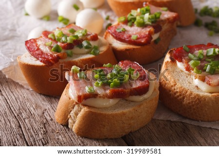 Italian crostini with bacon and mozzarella cheese close-up on the table. Horizontal