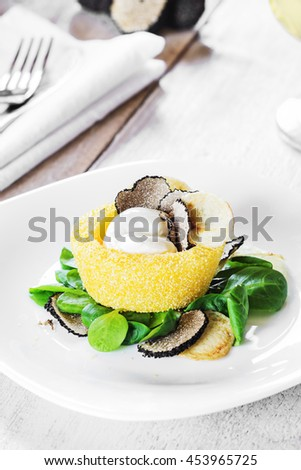 Italian cuisine- black truffle polenta basket with crispy chips and creamy sauce on a white plate. Selective focus. Vertical. - stock photo