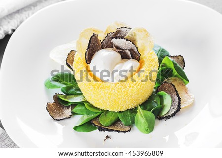 Italian cuisine- black truffle polenta basket with crispy chips and creamy sauce on a white plate. Selective focus.close up. - stock photo