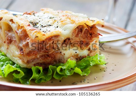 Italian cuisine. Freshly baked homemade lasagna with minced meat and cheese served on a piece of lettuce and red wine. - stock photo