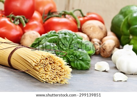 Italian cuisine ingredients of spaghetti, basil leaves, garlic, mushrooms, peppers and fresh tomatoes with extreme shallow depth of field.