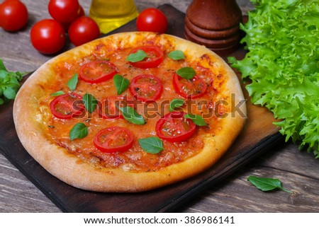 Italian cuisine. Mediterranean cuisine. Pizza Margherita with tomato topped with melted golden cheese, herbs and basil served  on old wooden table