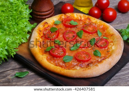 Italian cuisine. Mediterranean cuisine. Pizza Margherita with tomato topped with melted golden cheese, herbs and basil served on old wooden table - stock photo