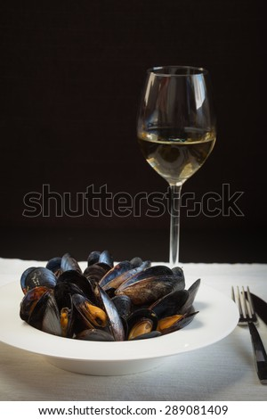 Italian cuisine. Mussels in a porcelain plate and a glass of wine. Shallow DOF, vertical, copy space - stock photo