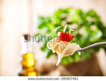 Italian cuisine. Pasta on fork. Pasta with olive oil, garlic, basil and tomatoes. Spaghetti with tomatoes - stock photo