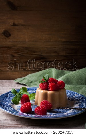 Italian dessert coffee panna cotta served on a blue plate with raspberries and fresh mint on vintage wooden bakground. Selective focus. Retro style toned.  - stock photo