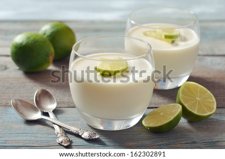 Italian dessert panna cotta with fresh lime in glass on wooden background - stock photo